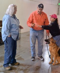 "Kim Wolf explains the use of the e-collar transmitter to her husband, Bennett, as Maryland Dog Spot trainer Linda Kaim helps with the explanation while ""Niki"" looks on."
