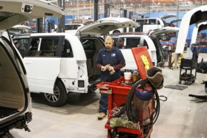 Tear down supervisor Justin Cawley removes parts from new minivans so that they can be converted to carry wheelchairs.