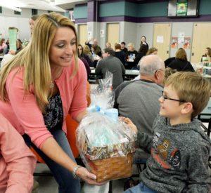 Sykesville Rotary president Dawn Wittfelt presents bingo winner Maxwell DeLuca, Eldersburg, with a prize basket.
