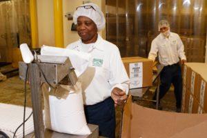 Gloria Harris does quality control while Brandon Porter packs seasoning blends.