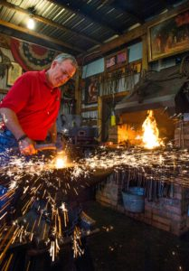 Ken Strosnider makes the sparks fly as he welds a piece of iron in his Detour forge where he creates decorative works of metal. Photo by Phil Grout.