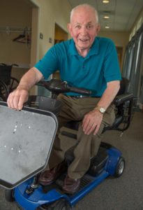 "John Staehlin of Carroll Lutheran Village demonstrates a modified ""scooter"" cart with adjustable food tray which he invented for a friend. The tray device allows his friend to move through a cafeteria line on his scooter as he receives food."
