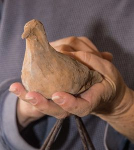 """Israelson holds one of 365 clay doves, part of a current installation at The Artist Gallery in Frederick, entitled """"Dove Cote: 365 Prayers for Peace""""."""